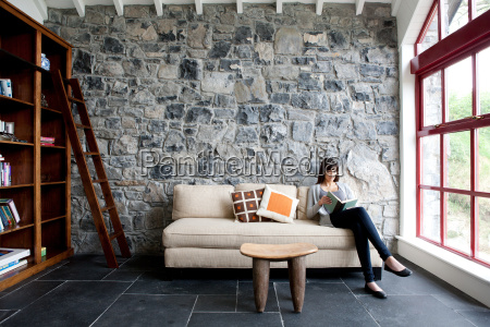 woman sitting and reading on sofa