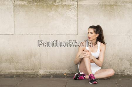 young female runner sitting on sidewalk