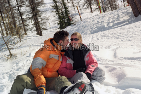 couple sitting in snow laughing