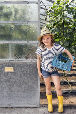 girl wearing wellingtons and hat standing