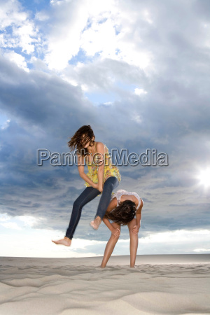 best friends play leapfrog at beach