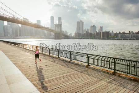 young female runner running along riverside