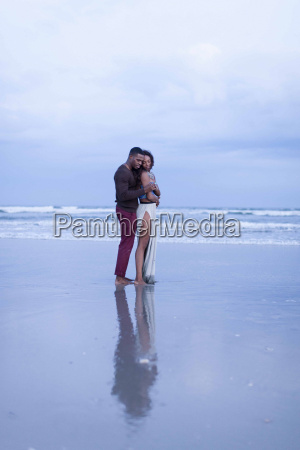 couple standing on beach hugging