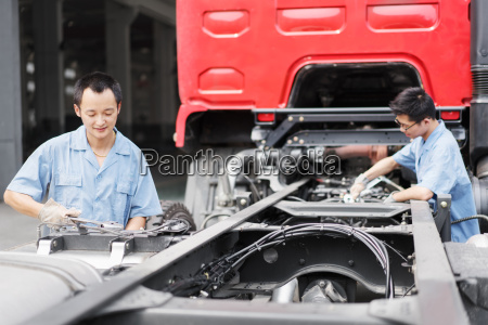 two male factory workers teamworking on