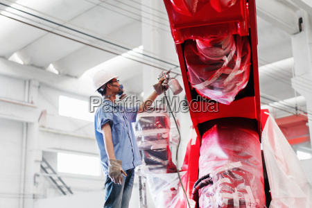 male factory worker spray painting a