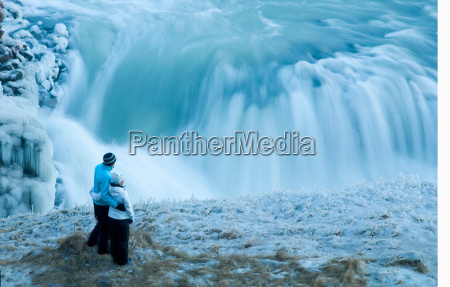 couple standing looking at waterfall