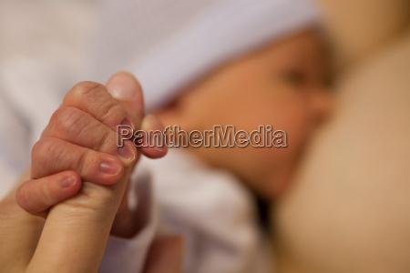 newborn baby boy gripping parents finger
