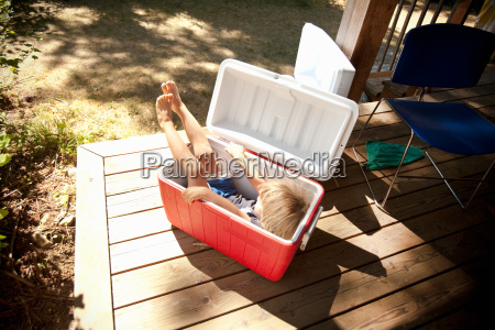 young boy sitting in cool box