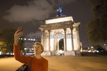 reife, weibliche, touristin, die, smartphone-selfie, von, wellington - 19532234