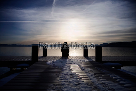 woman sitting on snowy pier at