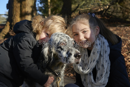 young brother and sister hugging dog