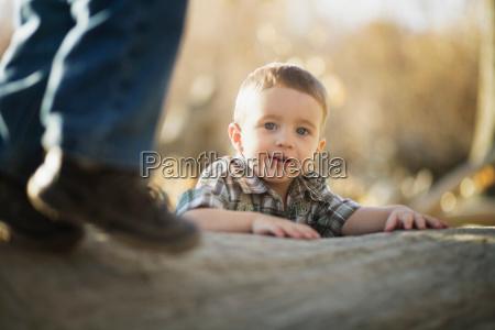 young boy climbing on log