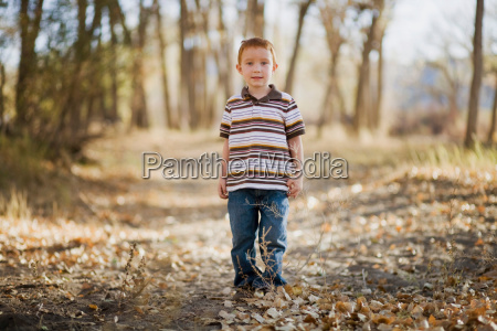 young boy standing in woods and