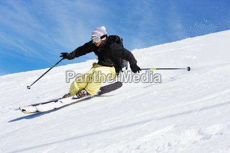 male skiing down mountain