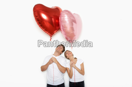 couple holding up heart balloons