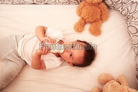 baby boy lying in crib drinking