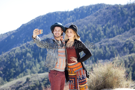 young couple using smartphone to take