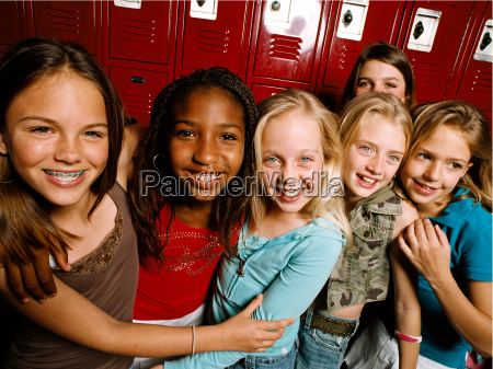 young friends standing together in school