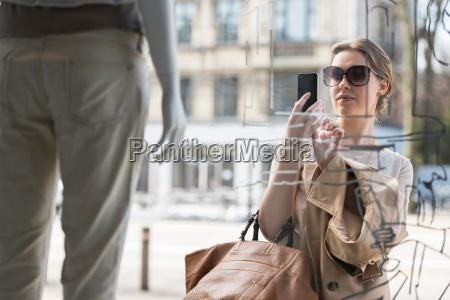 young woman photographing fashion mannequin outside