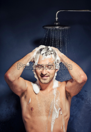 mid adult man shampooing hair under