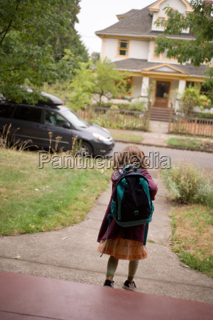 girl wearing backpack walking down path