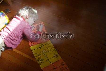 young boy lying on floor drawing