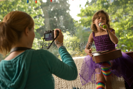 mother photographing daughter singing with microphone
