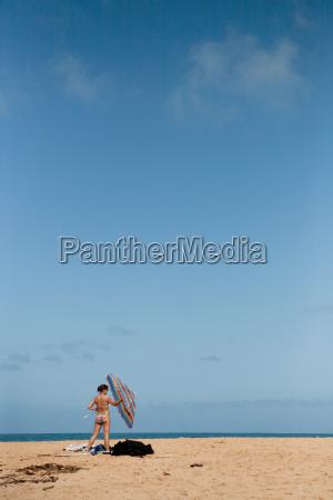 woman holding beach umbrella on beach