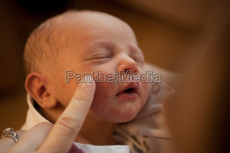mother touching newborn baby boys face