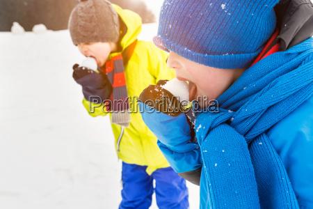two boys licking snowballs