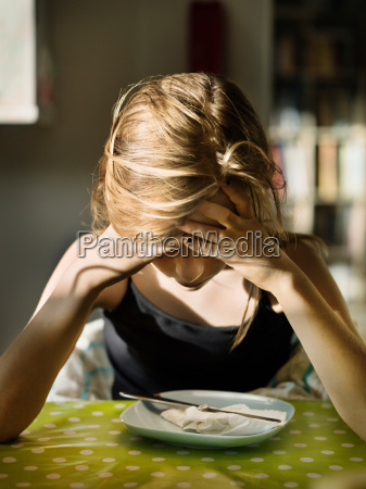 teenage girl sitting over plate with