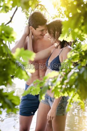 young couple behind foliage at lakeside