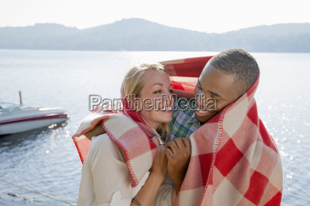 young couple wrapped in blanket by