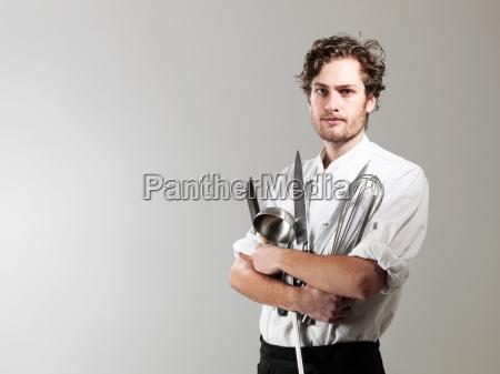 chef holding kitchen utensils against white