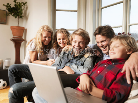family watching laptop together on sofa