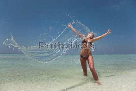 woman splashing in water at beach