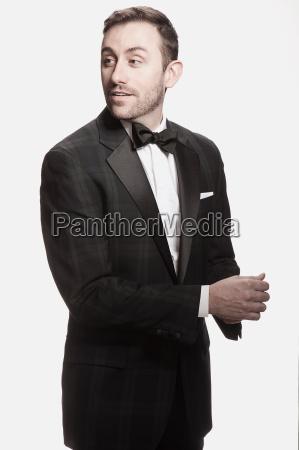 man in tuxedo standing against white