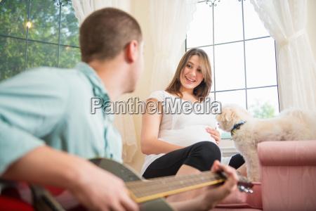mann spielt gitarre zu seiner schwangeren