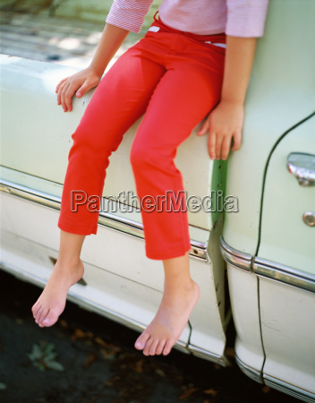 barefoot girl in red trousers sitting