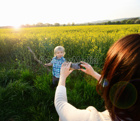 mother photographing son on smartphone in