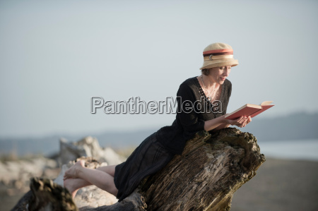 woman lying on driftwood reading a