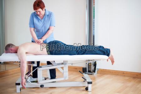 man lying on front on massage