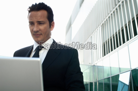 businessman working on laptop outside