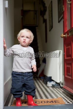 little boy standing in doorway of