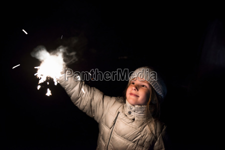 girl holding sparkler at night