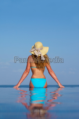 woman sitting in infinity pool