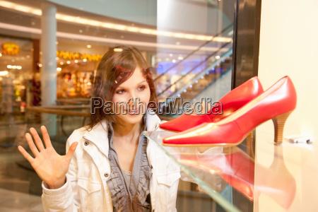 girl watching red shoes through showcase