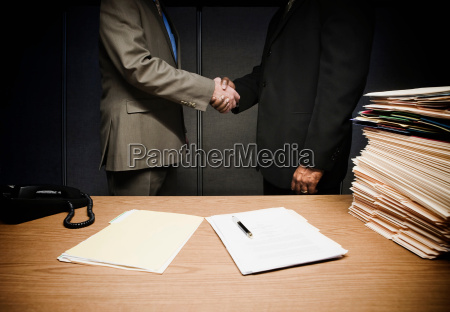 2 businessmen shaking hands at desk