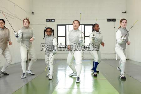 portrait of female fencers holding foils