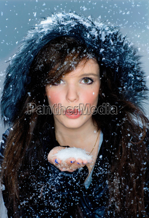 portrait woman blows snow from hand